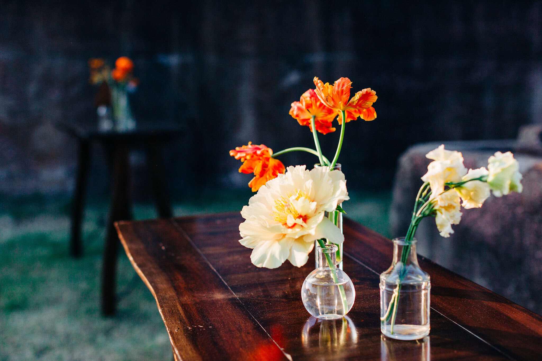 Simple bud vases with yellow peonies and orange ranunculus. Nashville event floral design.