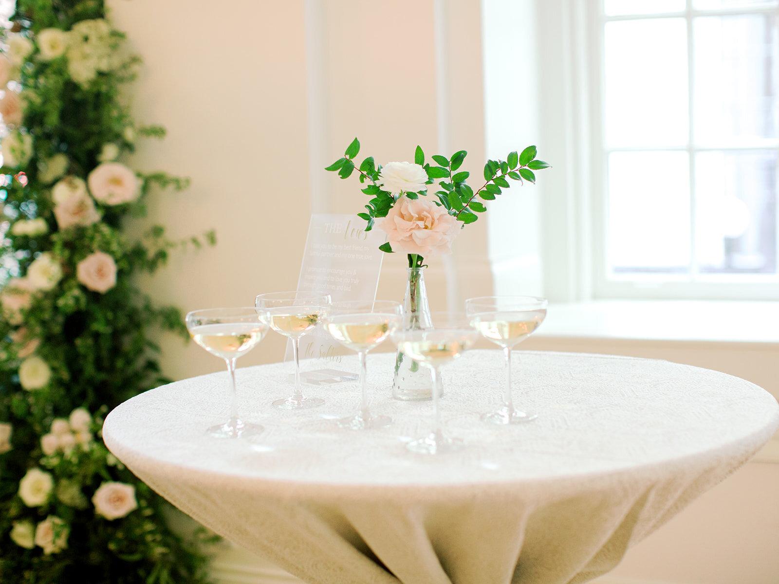 Simple blush flower bud vase with champagne. Nashville wedding florist.