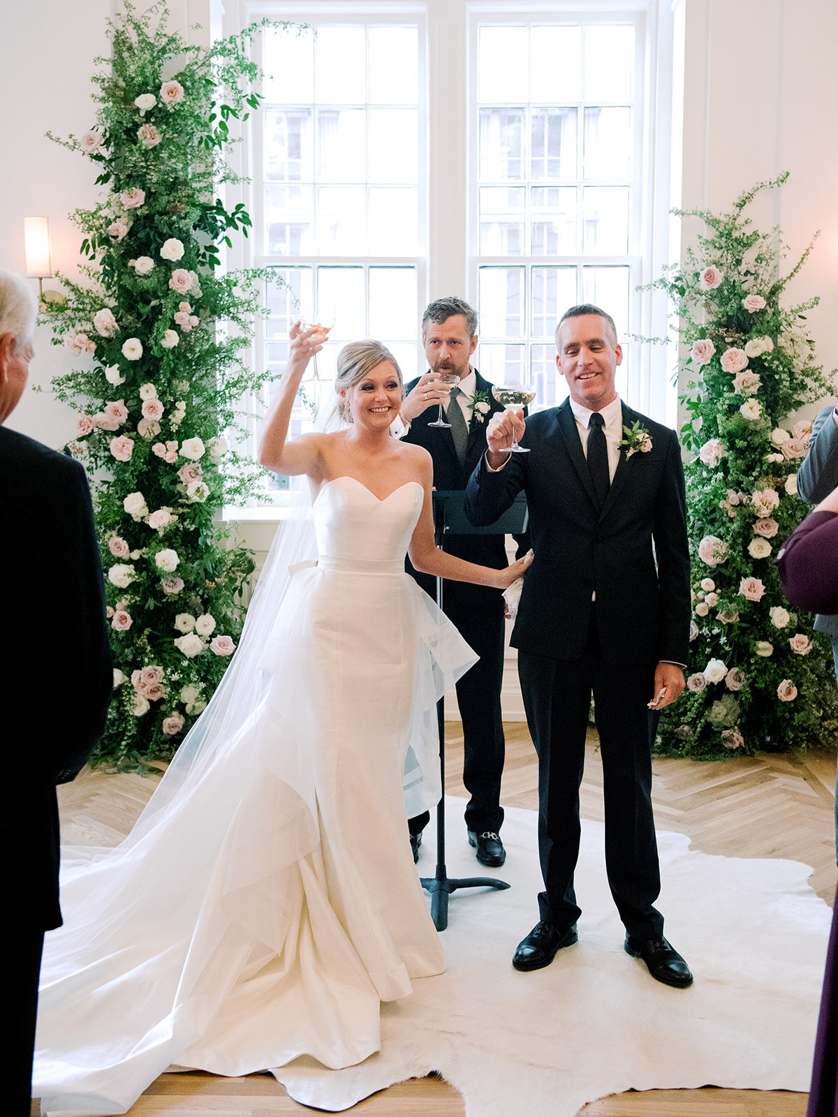 Champagne toast during wedding ceremony with blush and ivory floral installation in the Noelle. Nashville wedding floral design.
