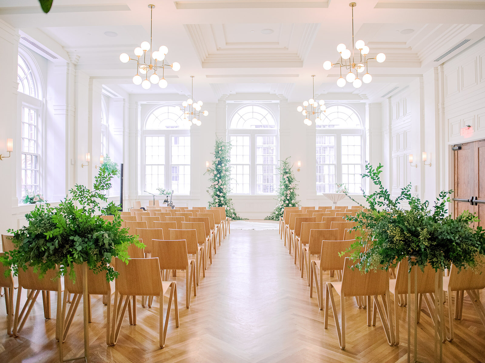 White wall venue with mid-century modern chandeliers and lush greenery floral installation for a Nashville wedding ceremony.