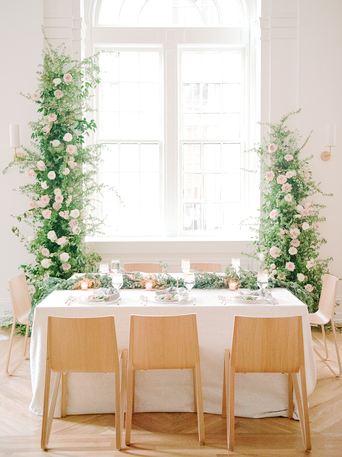 Sweetheart table with asymmetrical floral installation growing up either side of the windows in the Noelle. Nashville Wedding Florist.