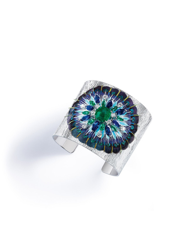 """This Piaget """"Serenissima""""cuff is so stunning beautiful and unique. It is encrusted with emeralds, sapphires and diamonds, and has an unexpected material: 10 different kinds ofreal feathers!  The center stone is a 3.46 carat Columbian cushion Emerald..  .It took over250 hours to complete and cost around$360,000.   PHOTO:PIAGET"""