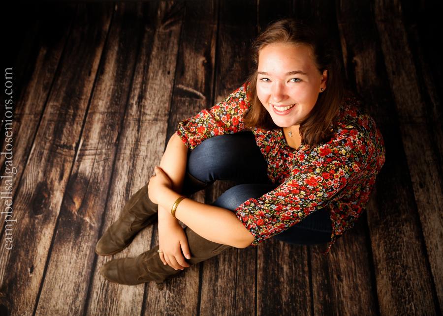 Portrait of high school senior on wooden floor background by teen photographers at Campbell Salgado Studio in Portland, Oregon.