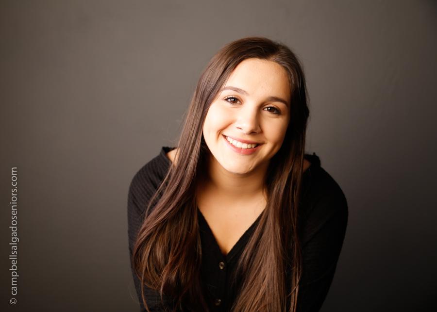 High school senior portrait photography of teen on grey background by photographers at Campbell Salgado Studio in Portland, Oregon.