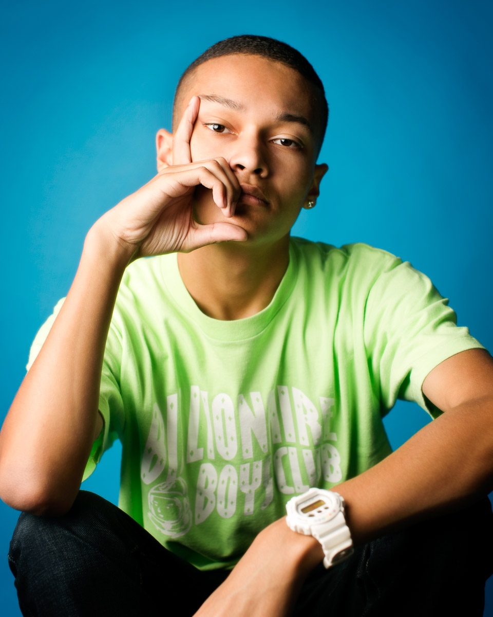 High school senior photography of a young man against a blue background by Campbell Salgado Studio.