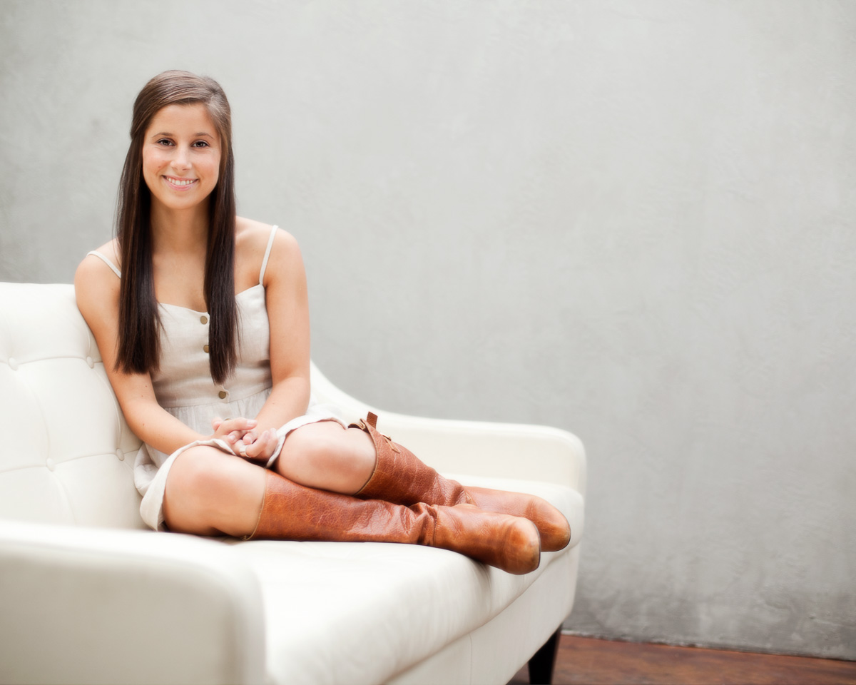 High school senior picture of a young woman sitting on a couch against a gray background, photographed by the Portland high school senior photographers at Campbell Salgado Studio in Portland, Oregon