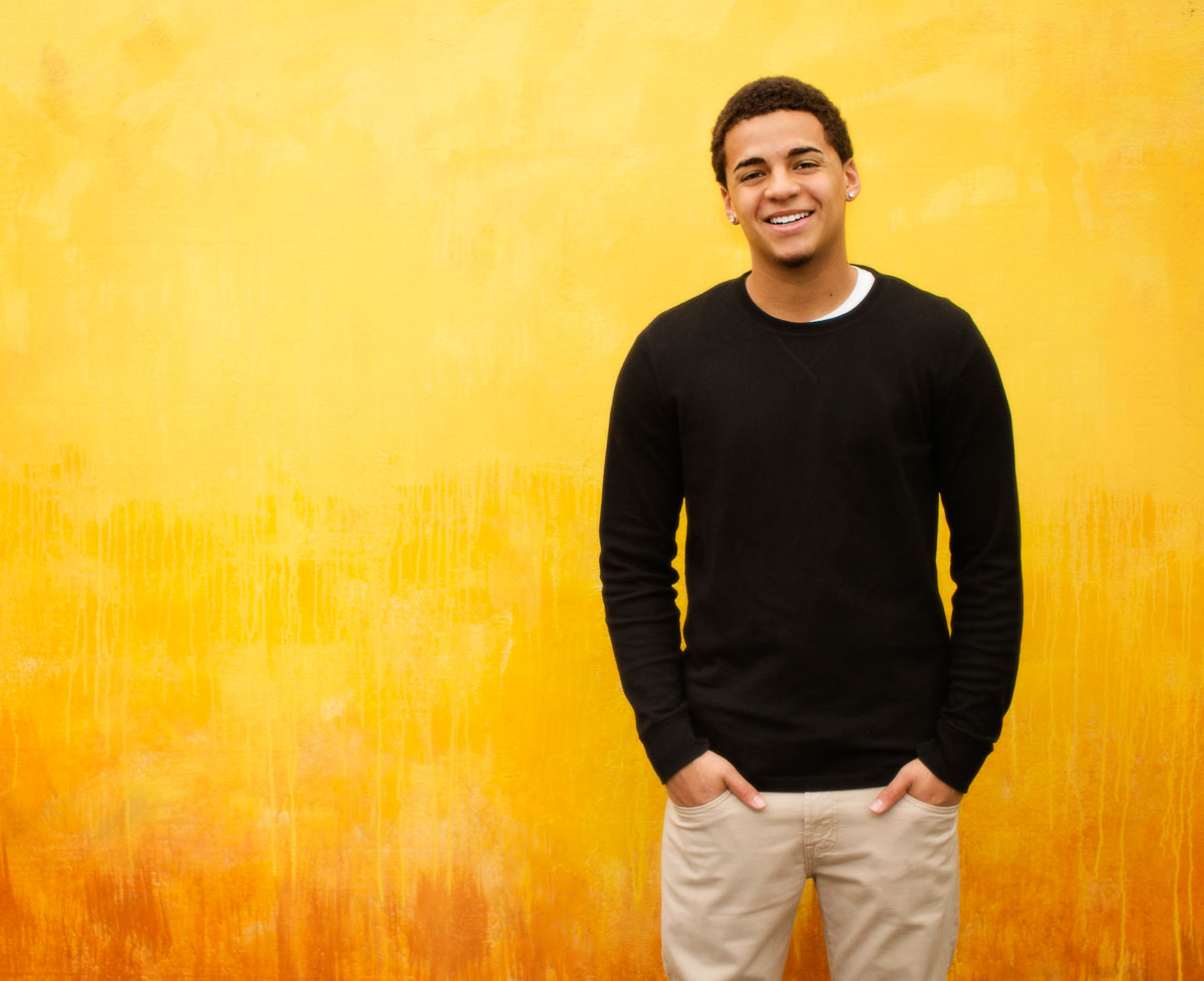 High school senior photography of a young man standing in front of a yellow background, photographed by the Portland high school senior photographers at Campbell Salgado Studio in Portland, Oregon