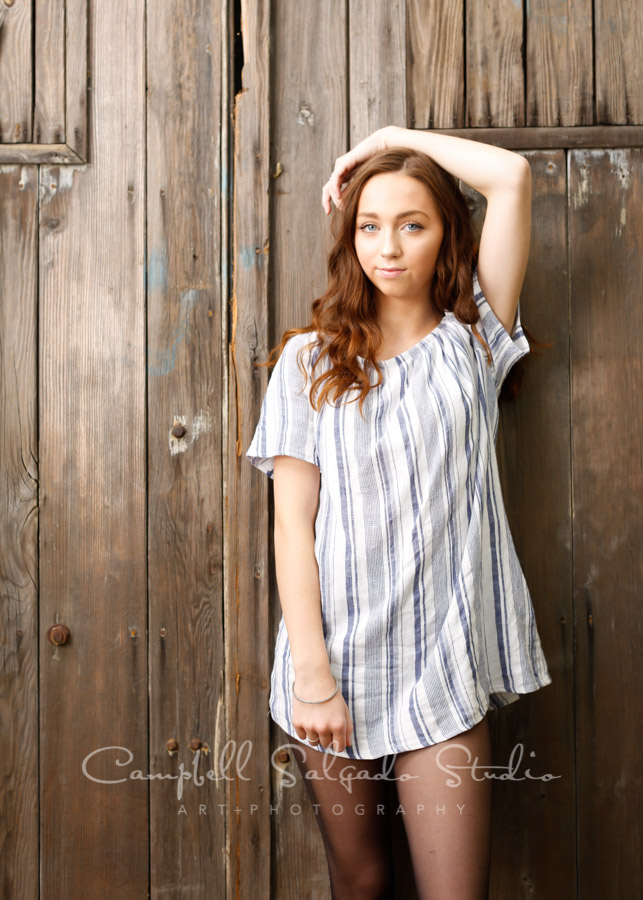 High school senior pictures of a young woman standing in front of a barn doors background by senior photographers at Campbell Salgado Studio in Portland, Oregon.