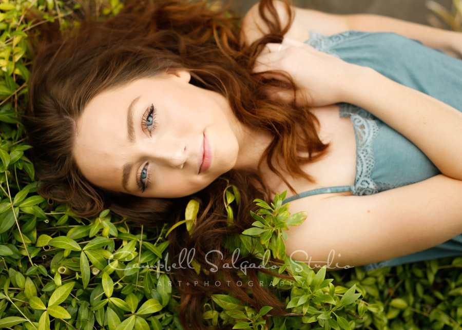 Senior picture of a young woman in garden background by high school senior photographers photographers at Campbell Salgado Studio in Portland, Oregon.