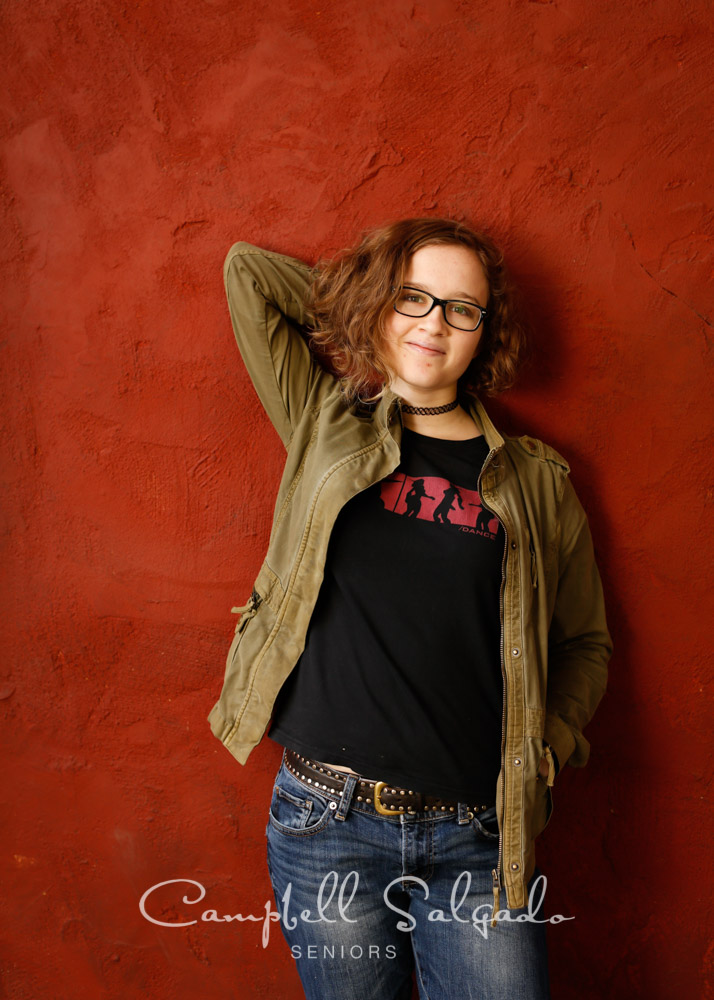 Portrait of HS senior on red stucco background by teen photographers at Campbell Salgado Studio in Portland, Oregon.