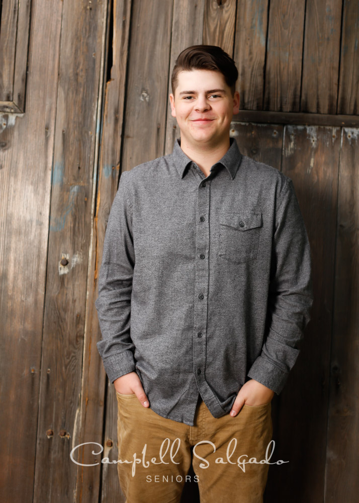 High school senior portrait photography of teen on barn doors background by senior picture photographers at Campbell Salgado Studio in Portland, Oregon.