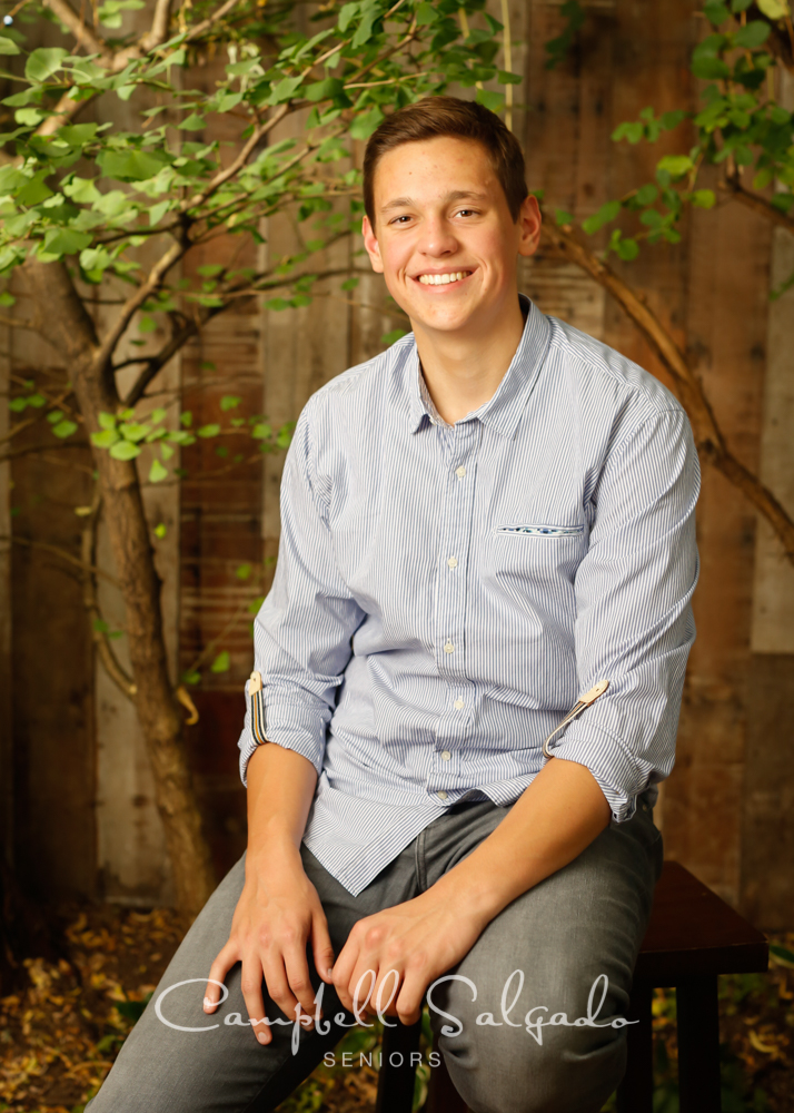 Senior portraits outside of a young man in front of a wooden wall background by high school senior picture photographers photographers at Campbell Salgado Studio in Portland, Oregon.