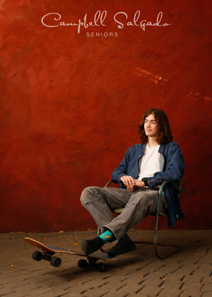 Portrait of young man against a red stucco background by Portland senior picture photographer Kim Campbell of Campbell Salgado Studio in Portland, Oregon.