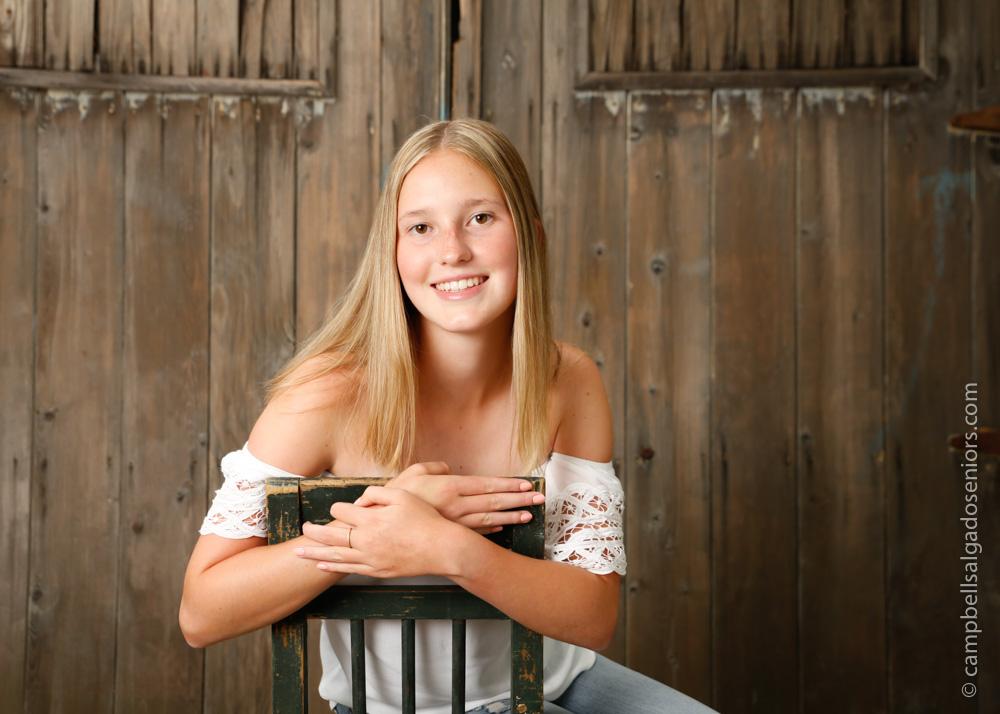 High school senior portrait photography of teen on barn doors background by senior picture photographers at Campbell Salgado Studio in Portland, Oregon.