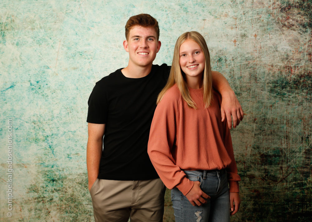 Senior portraits, Portland Oregon of teens in front of a weathered green background by photographers at Campbell Salgado Studio.