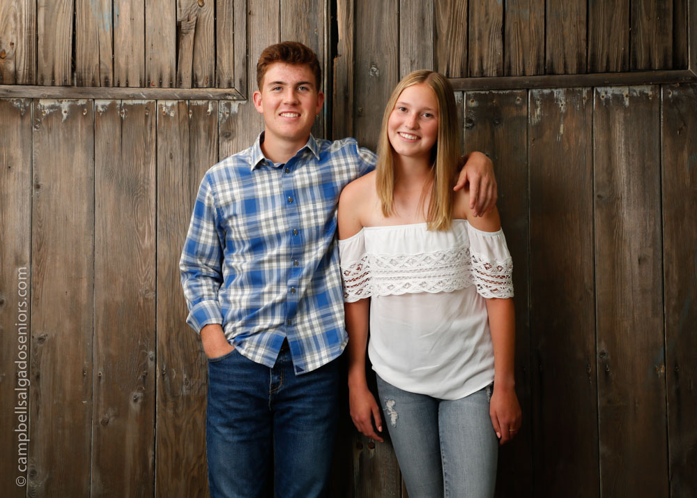 Senior portraits outside of teens in front of barn doors background by high school senior picture photographers photographers at Campbell Salgado Studio in Portland, Oregon.