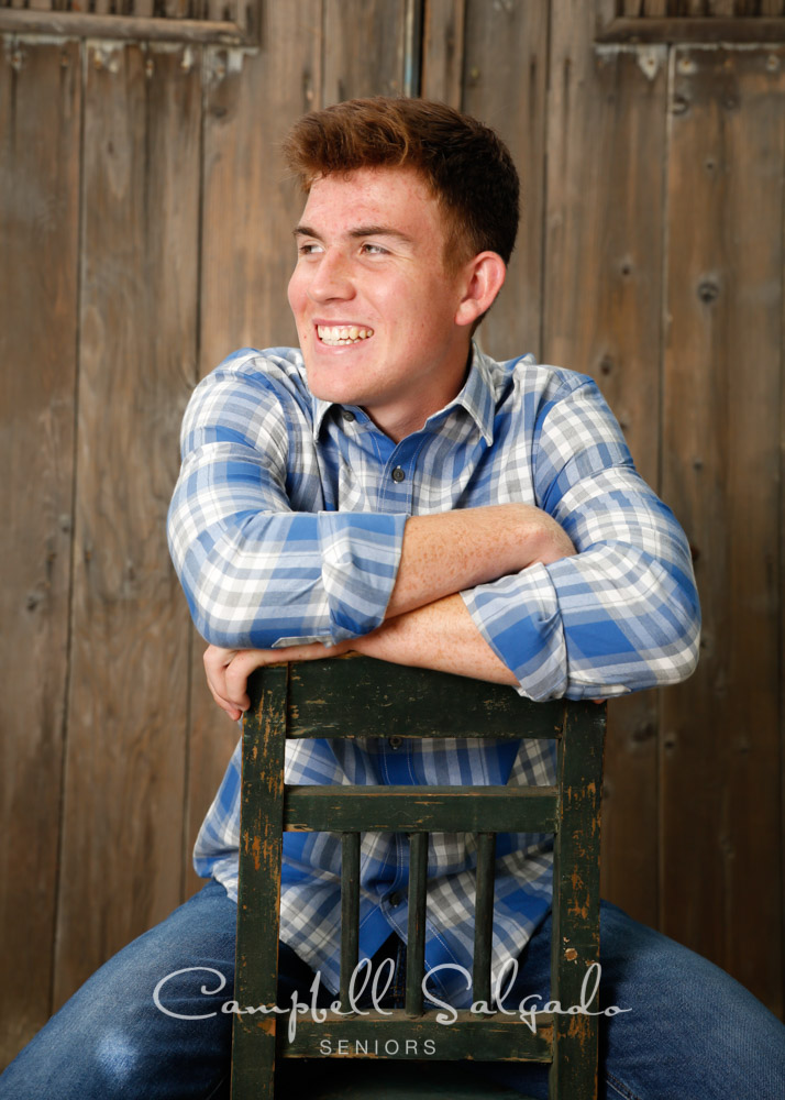 Senior pictures outside of a young man in front of a barn doors background by high school senior portrait photographers photographers at Campbell Salgado Studio in Portland, Oregon.