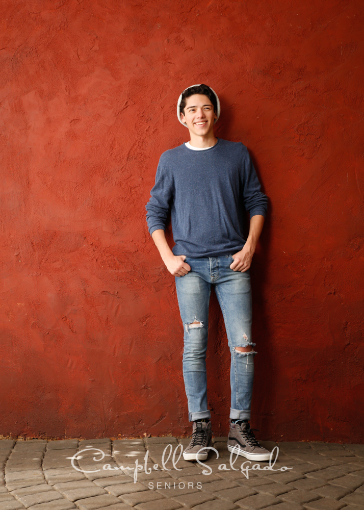 High school senior pictures of a young man standing in front of red stucco background by senior photographers at Campbell Salgado Studio in Portland, Oregon.