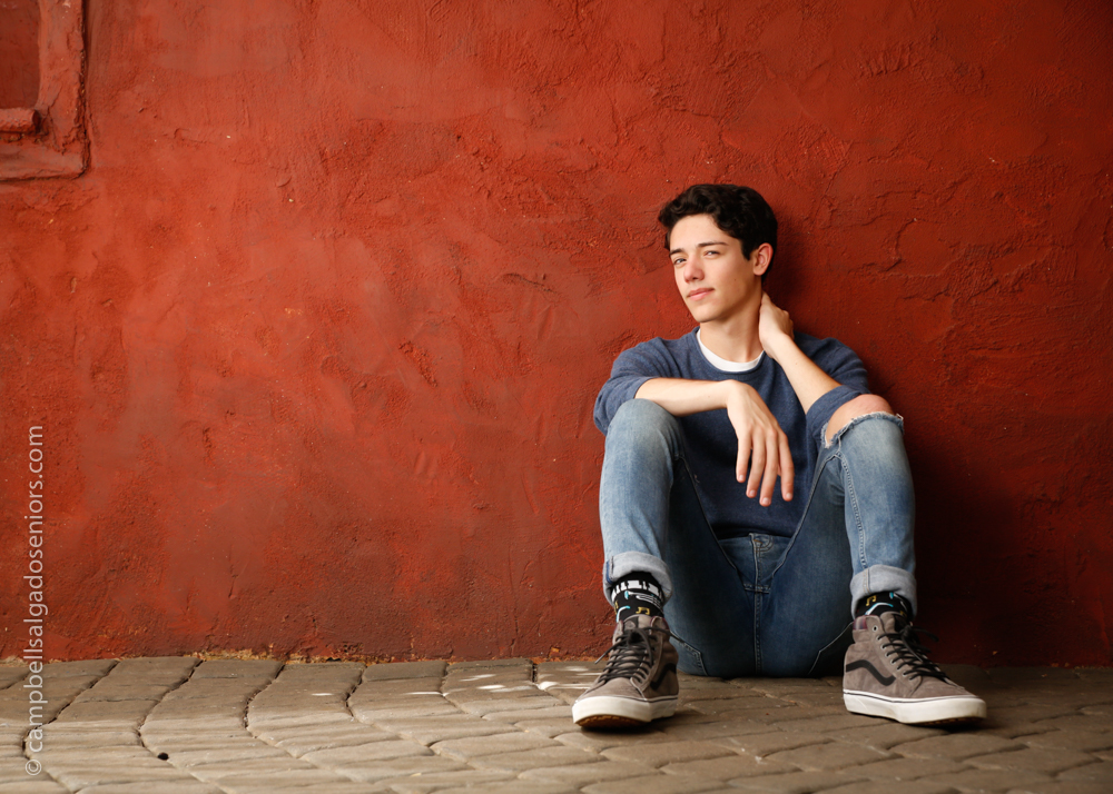 Senior picture of a young man in red stucco background by high school senior photographers at Campbell Salgado Studio in Portland, Oregon.