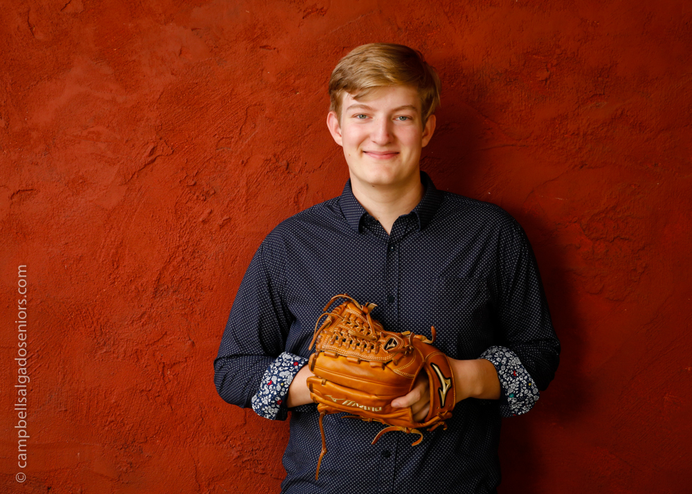 Portrait of young man against a red stucco background by Portland photographers - senior pictures at Campbell Salgado Studio in Portland, Oregon.