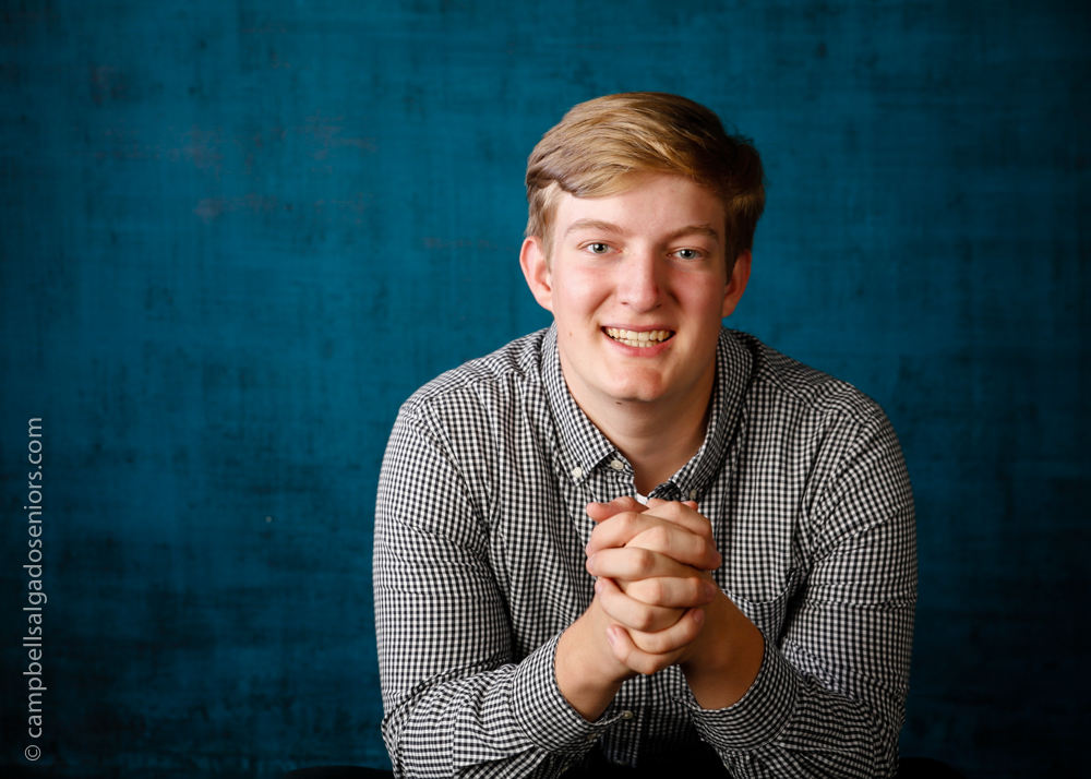 Senior pictures of a young man in front of a deep ocean background by high school senior portrait photographers photographers at Campbell Salgado Studio in Portland, Oregon.