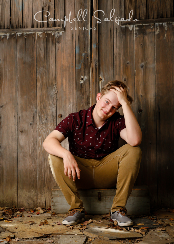 Senior portraits, Portland Oregon of young man in front of a barn doors background by photographers at Campbell Salgado Studio.