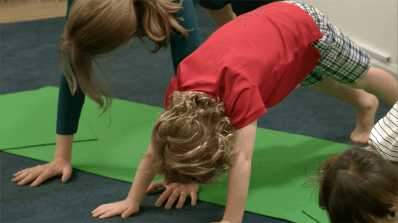 Children practicing downward facing dog yoga pose in a classroom