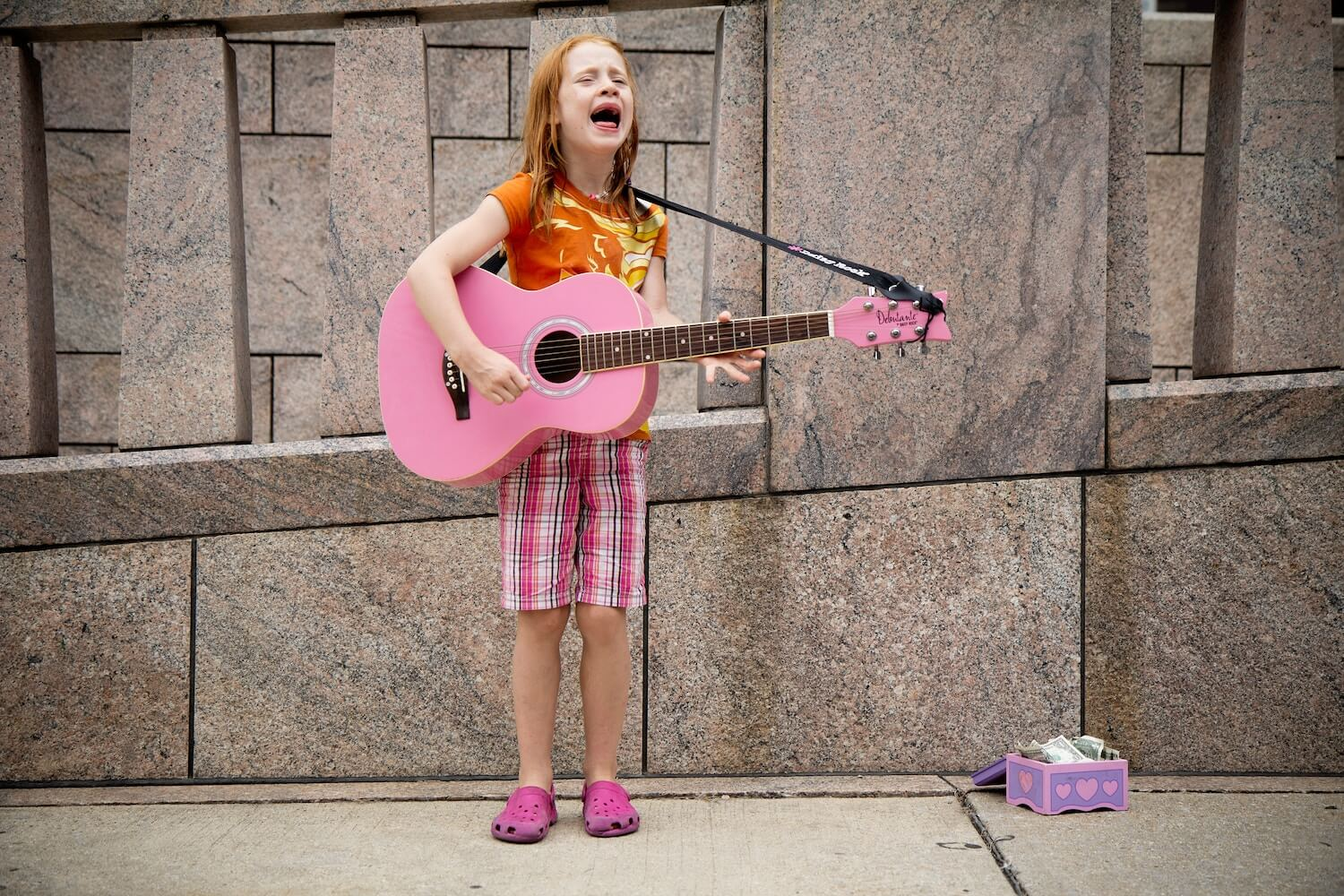 Child singing with a pink guitar Photo by  Felix Koutchinski  on  Unsplash