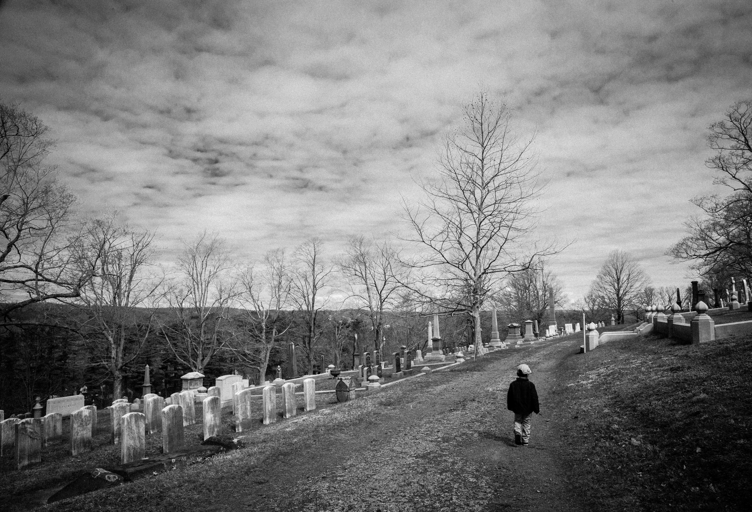 "Indian Hill Cemetery, 2015  This shot reminds me of Neil Gaiman's, ""The Graveyard Book.""  Gaiman is one of my favorite authors and I often thought of that book when I took walks through this cemetery.  When my son, Cormac, walked ahead of me on the path scenes from that book immediately came to mind."