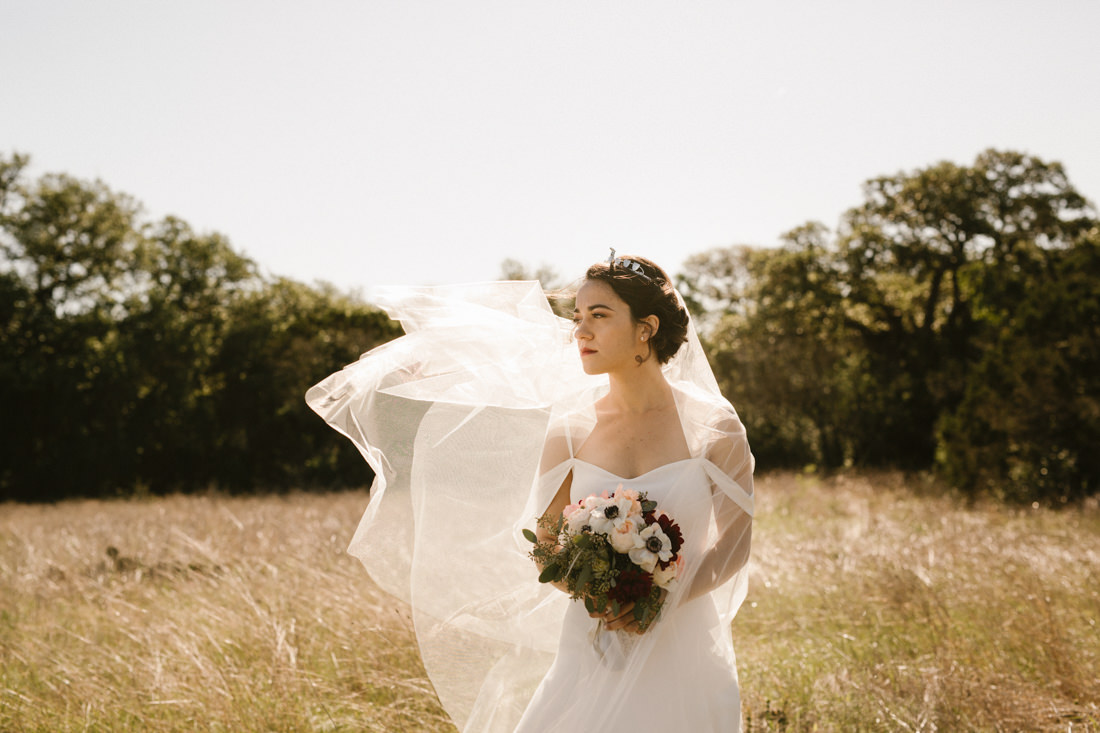 Bride with veil in the wind in hill country forest.