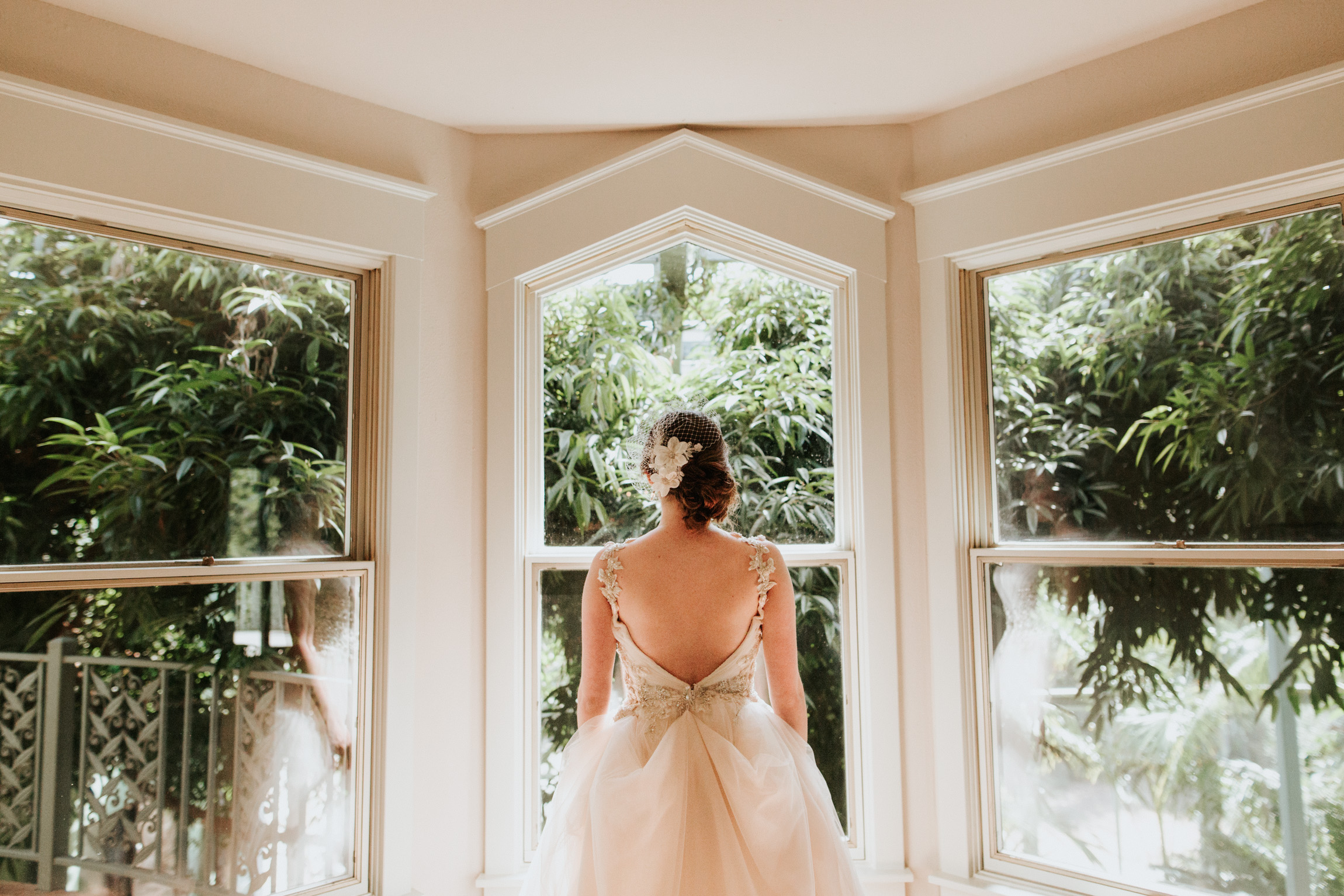 Bride looking out of the window at Greenhouse at Driftwood Wedding