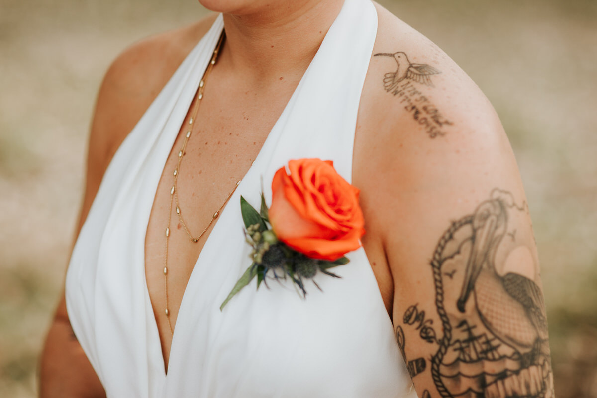 Close-up of tattooed bride's jumpsuit at Ranch Austin wedding