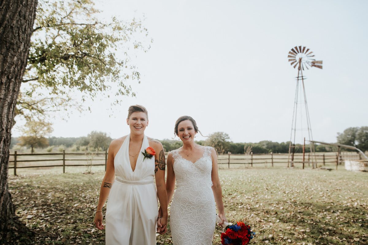 Two brides holding hands at Ranch Austin wedding
