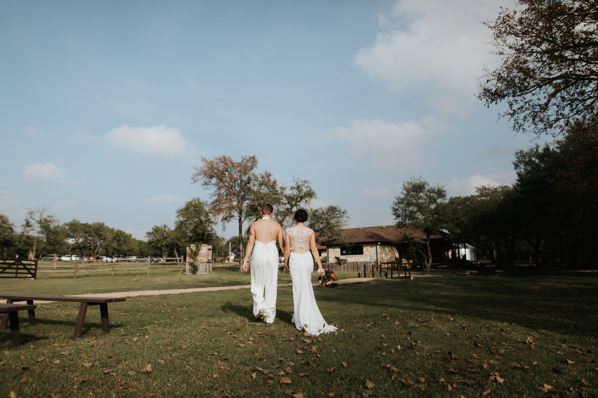 Same sex couple holding hands walking into a field at Ranch Austin wedding