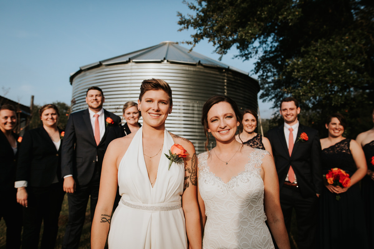 Brides with wedding party in front of farm silo at Ranch Austin wedding