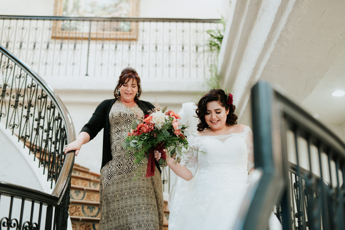 Bride coming down staircase with mother