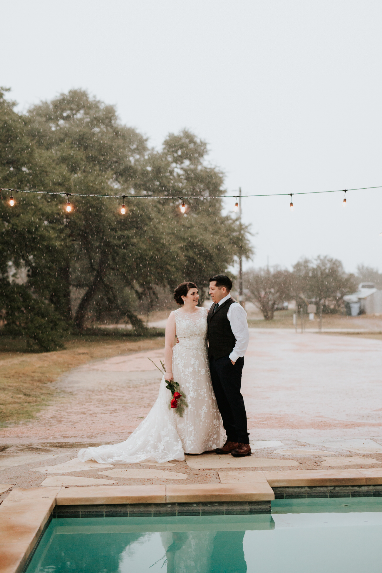 Bride and groom by pool at Christmas wedding