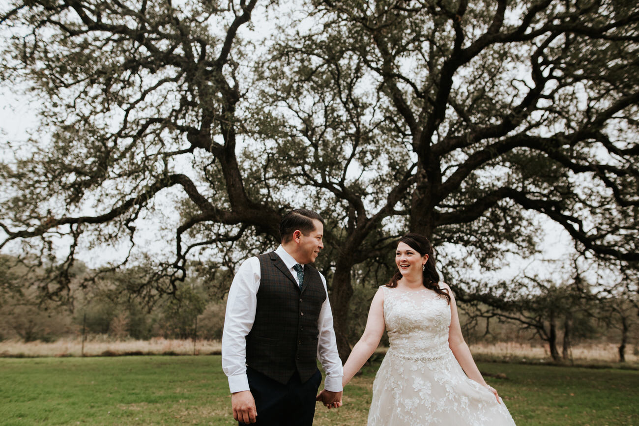 Bride and groom holding hands in front of beautiful tree