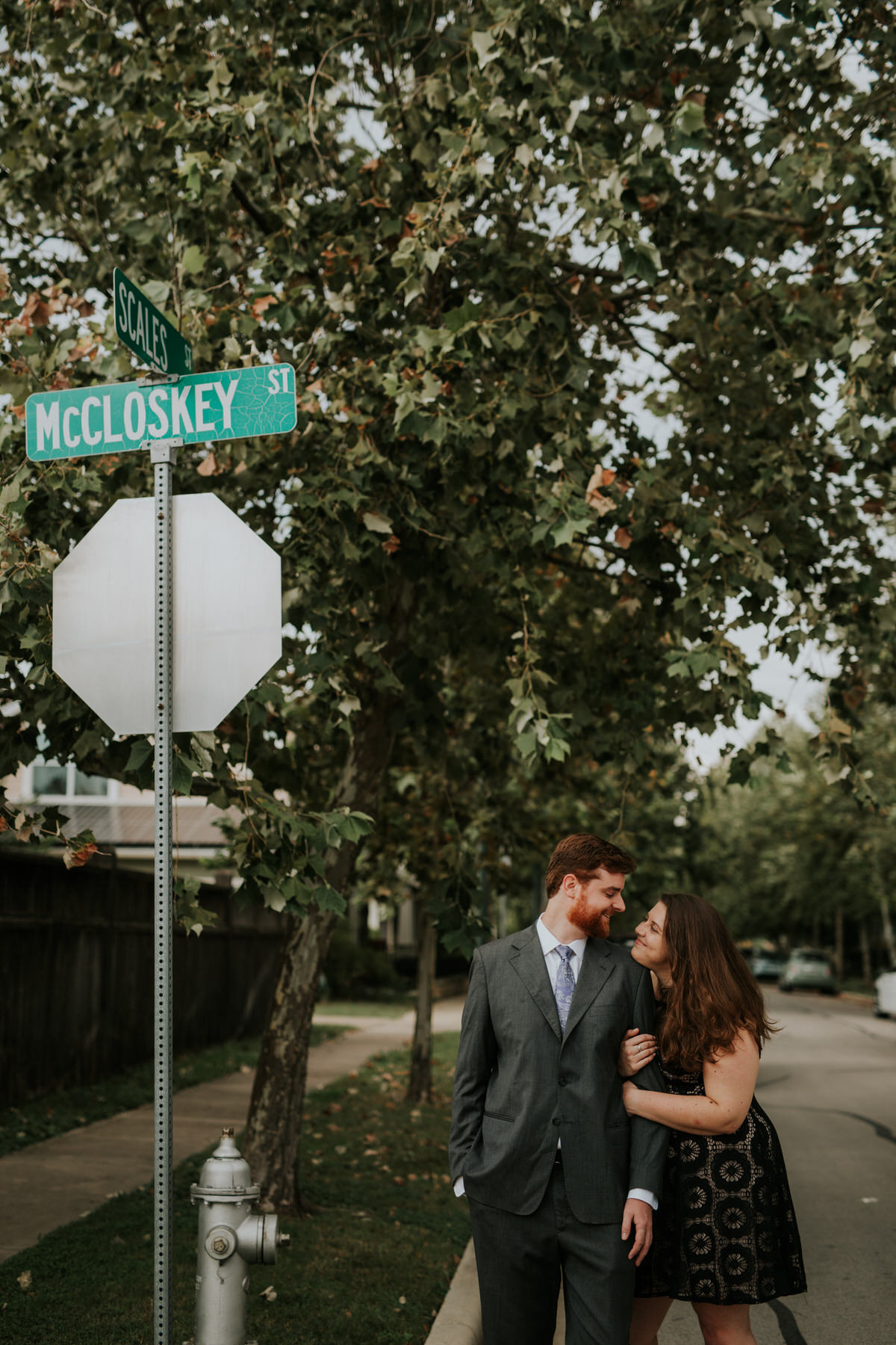 Couple hugging in front of street sign