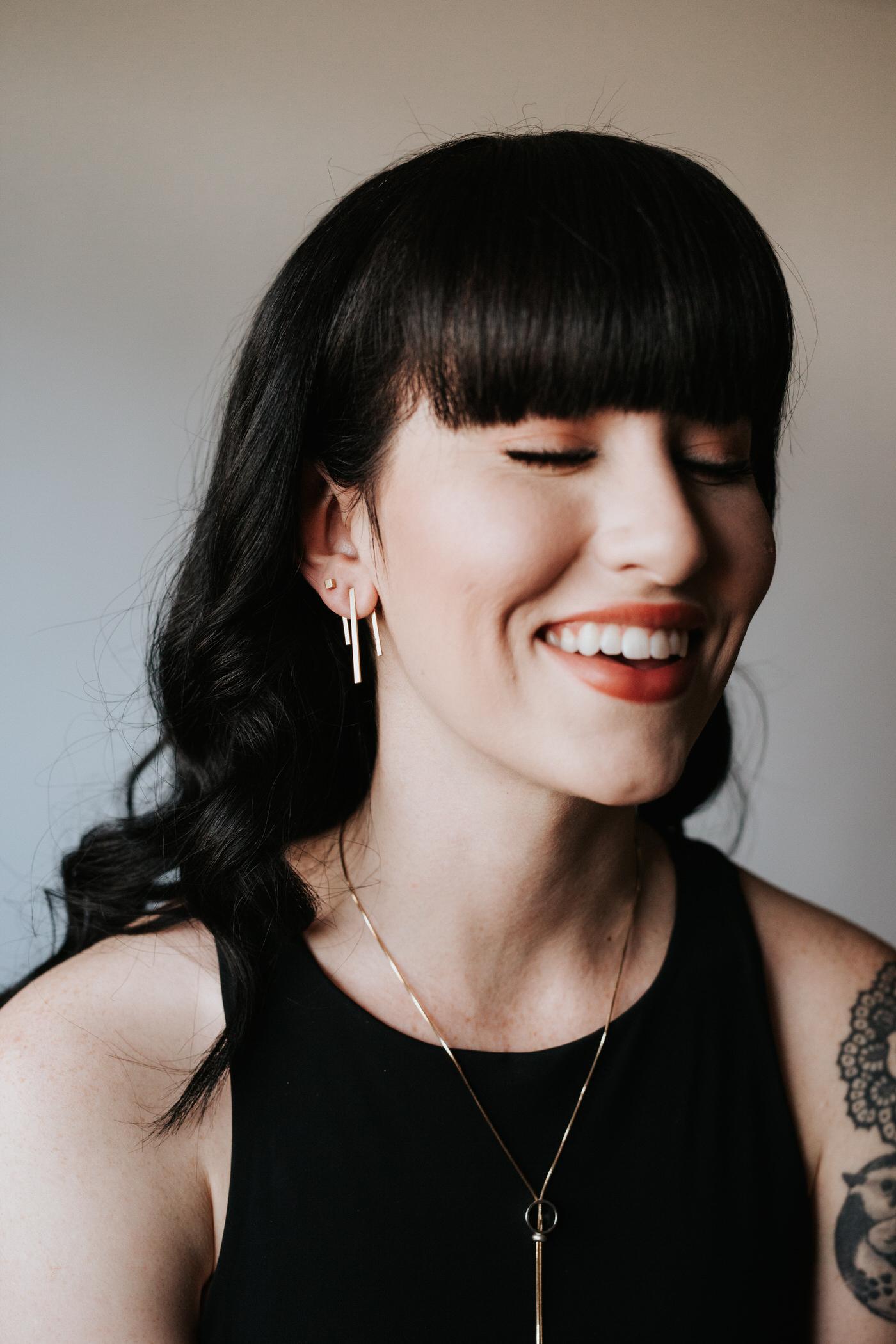 Tattooed model wearing beautiful, geometric Rebekah Vineyard Jewelry