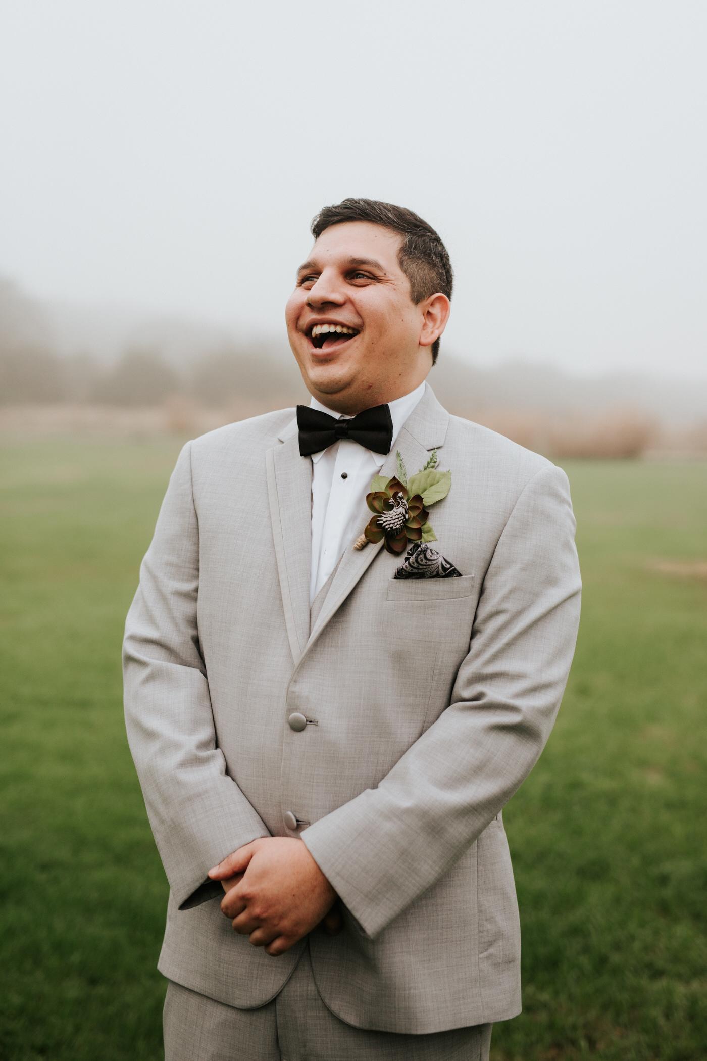 Groom laughing at Pecan Springs Ranch wedding