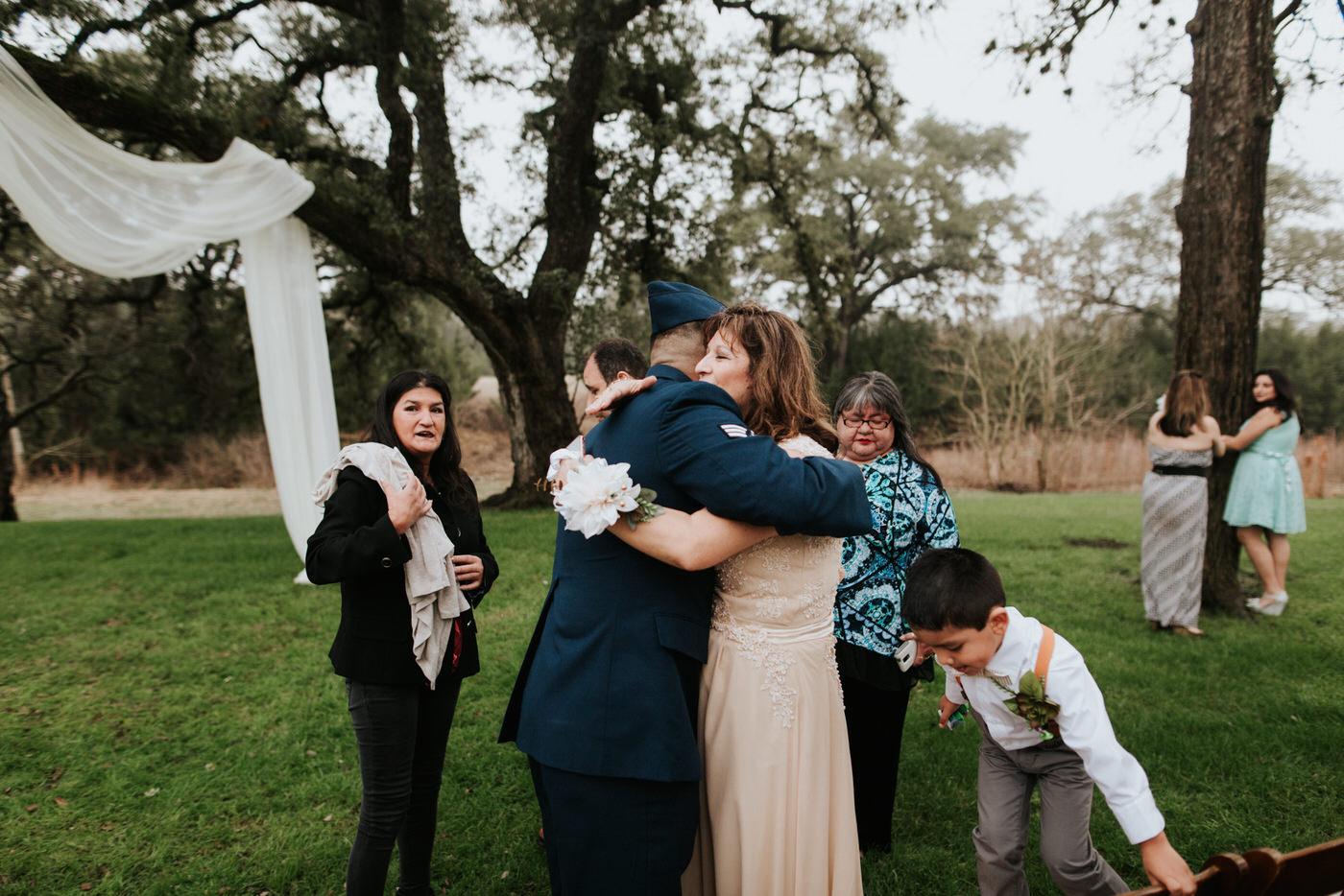 Wedding guests hugging at Pecan Springs Ranch