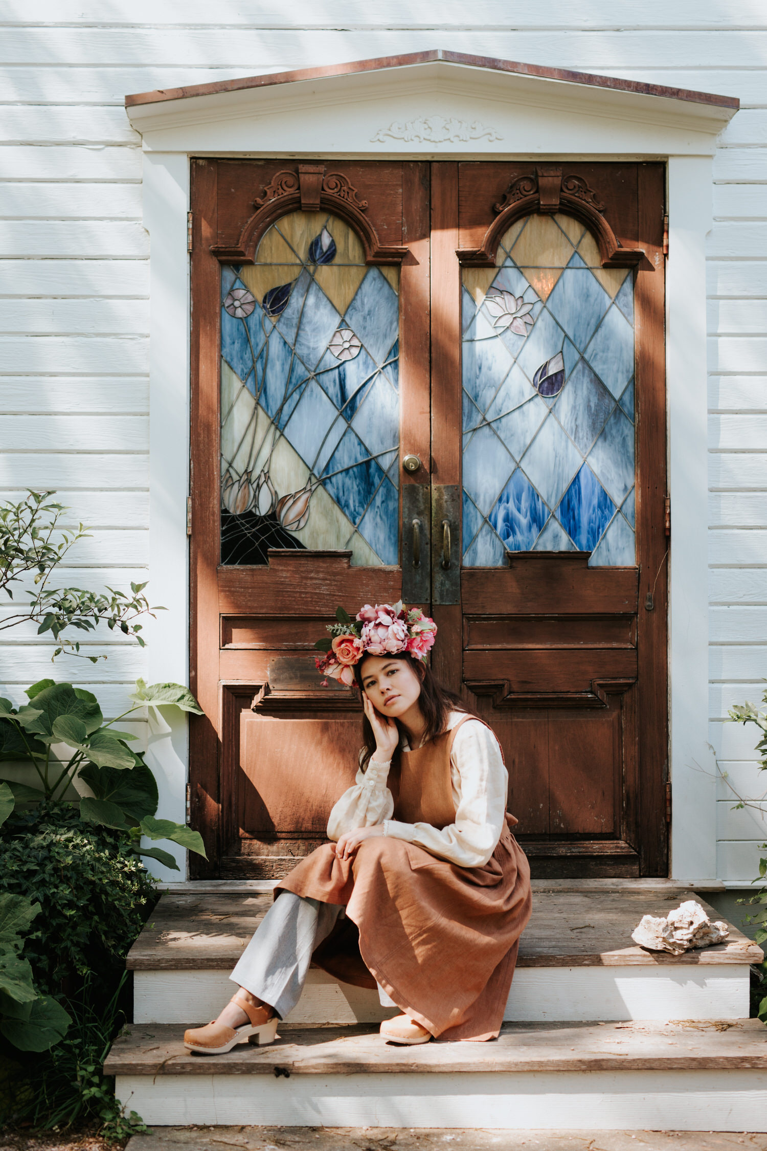 Model in flower crown and vintage clothing in front of stained glass