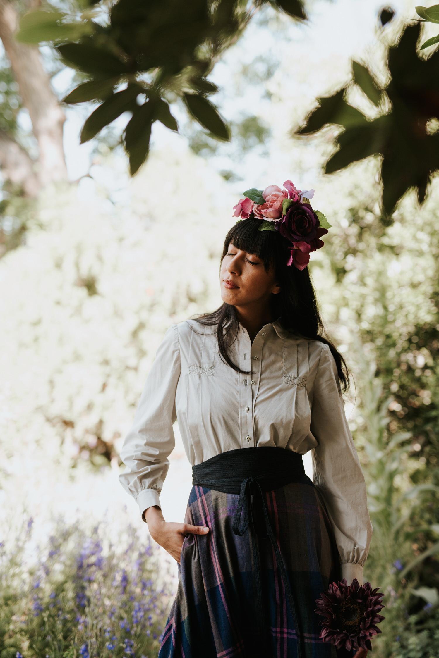 Woman in flower crown in field of cornflowers