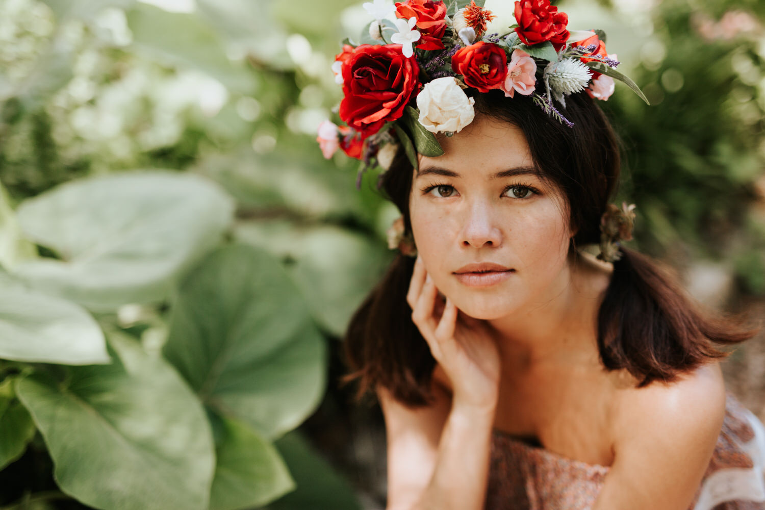 Woman in rose flower crown surrounded by plants