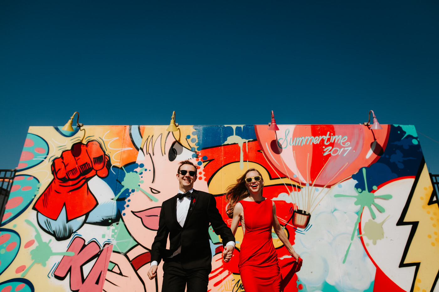 Happy engaged couple at Coney Island boardwalk with colorful mural