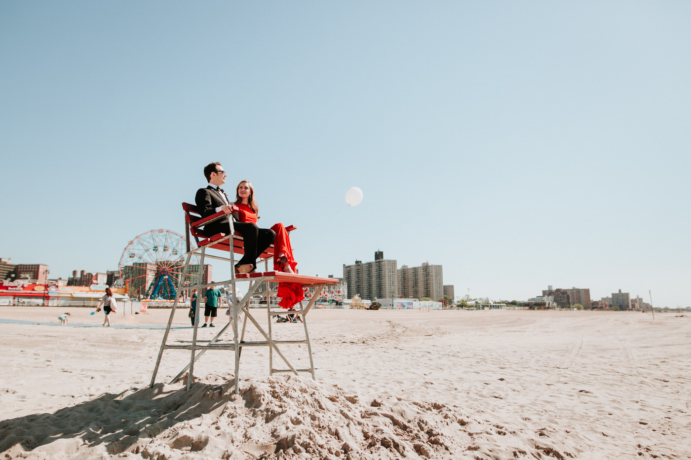 Engaged couple in a Coney Island lifeguard stand on the beach