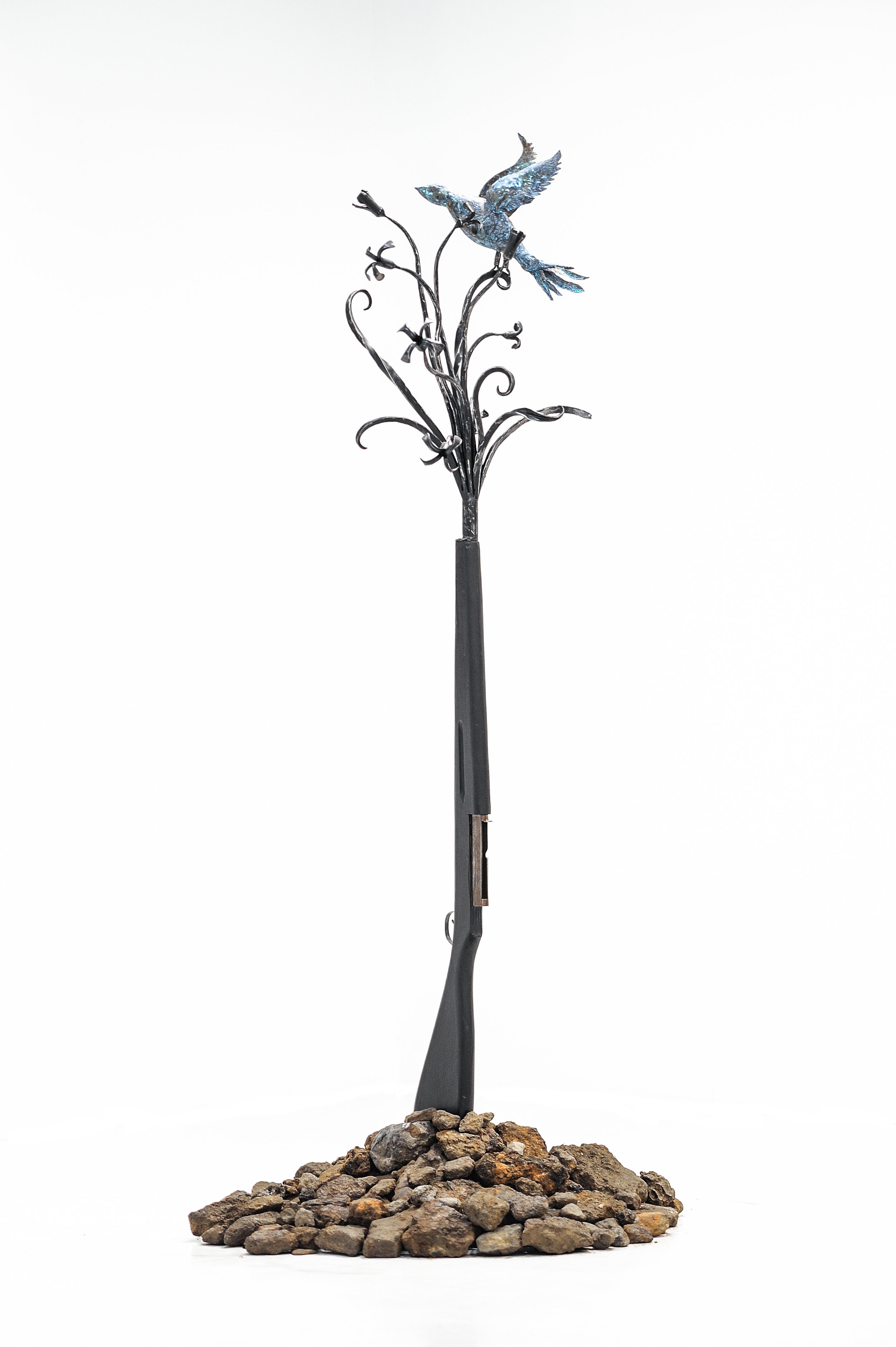 """Blood of the Earth  , 2019, recycled gun and guns barrels, forged steel, rocks, gun dimensions: 60"""" x 15"""" x 14"""""""