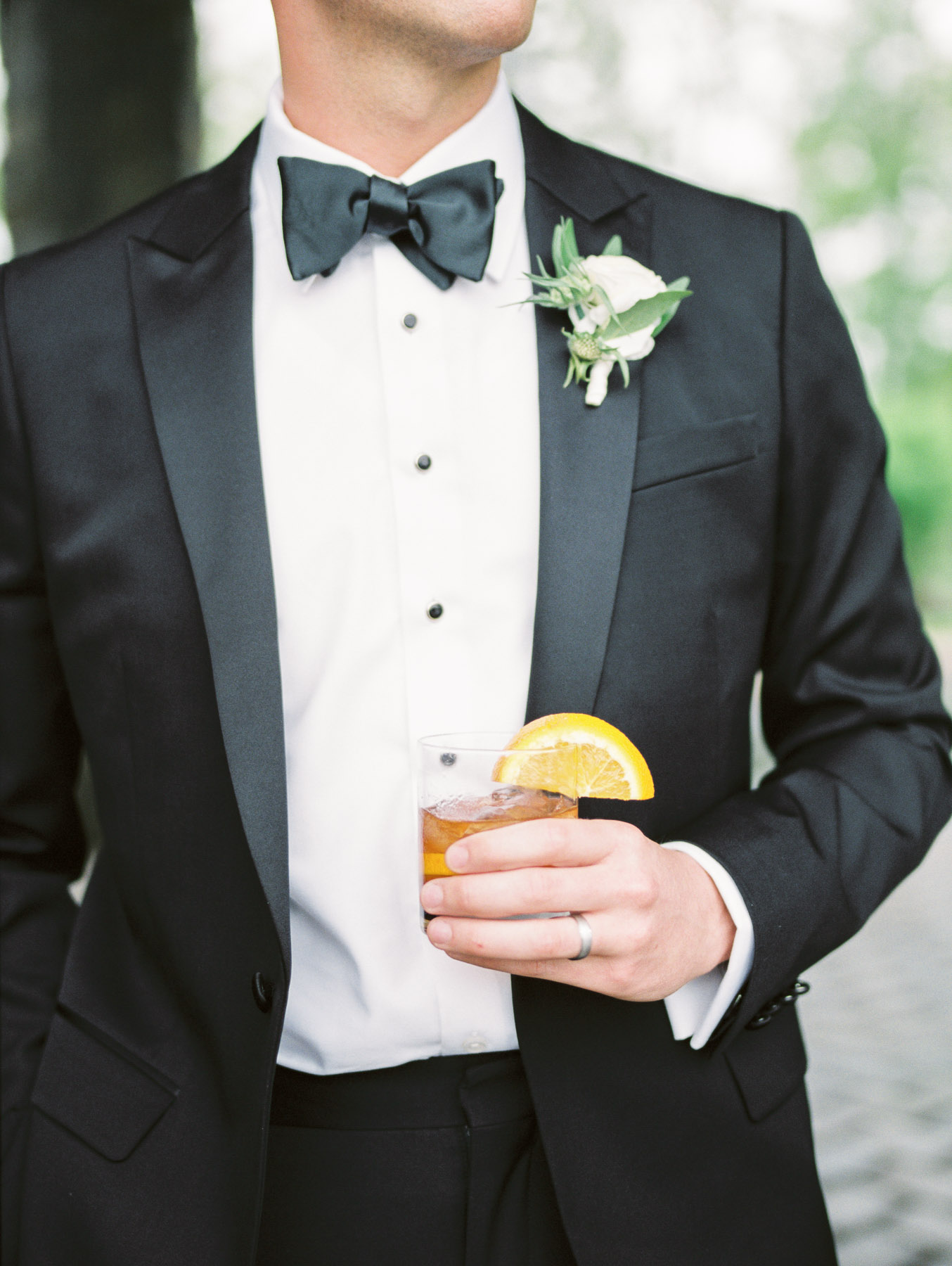 Groom holding specialty wedding day cocktail