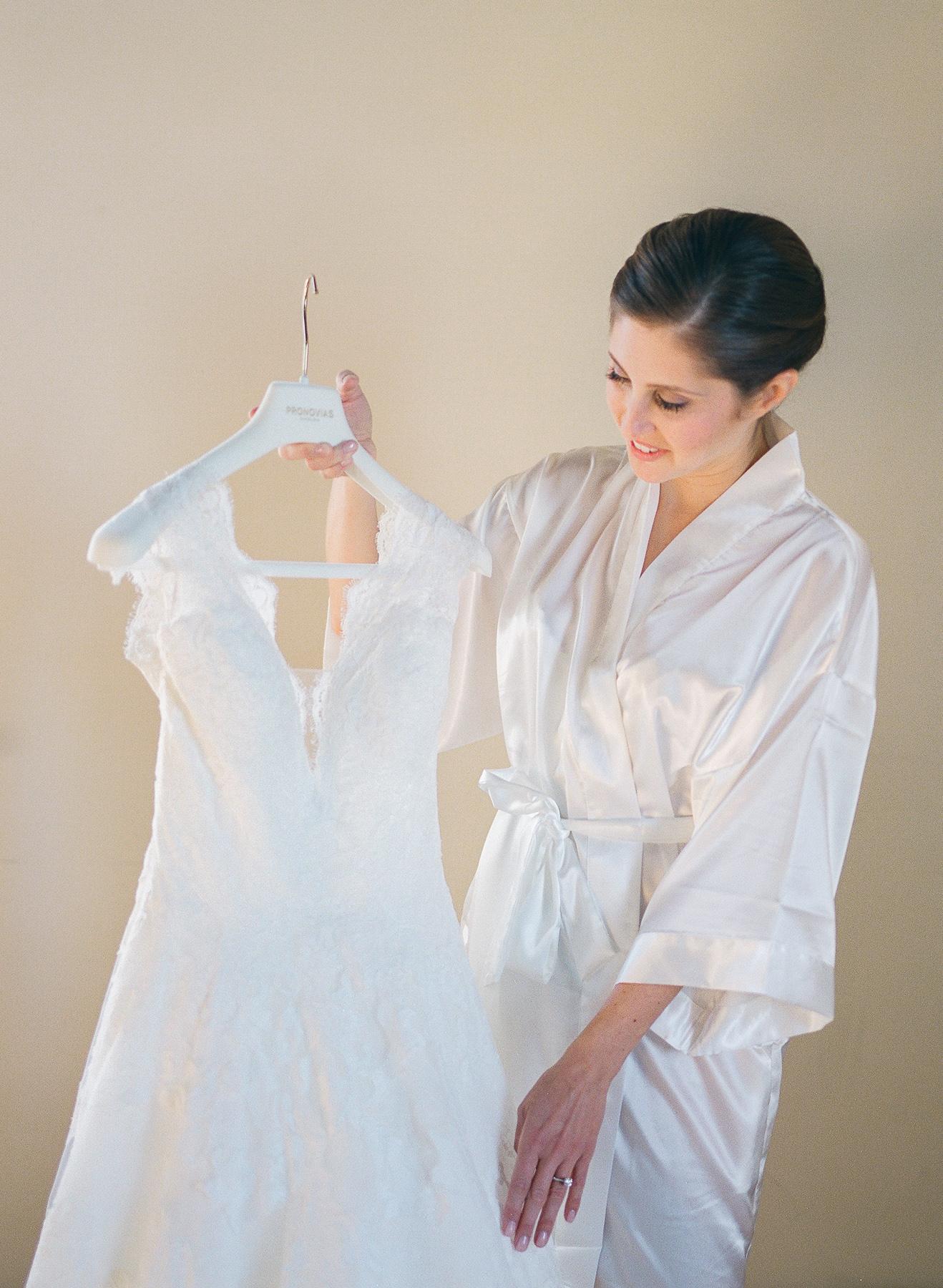 Bride admiring wedding gown